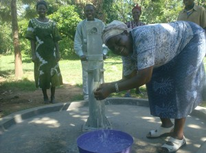 The Water Project : emusembe-upc-chairlady-tossing-water_web