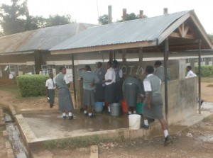 The Water Project : mukumu-girls-high-school-students-struggling-to-collect-piped-water-from-a-spring