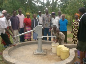 The Water Project : emulundu-community-well-water-flowing-during-hand-over