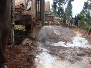 The Water Project : kwa-maji-community-based-organisation-flashing-of-the-well-during-drilling