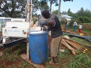 The Water Project : kwa-maji-community-based-organisation-mixing-of-drilling-form-during-drilling-process