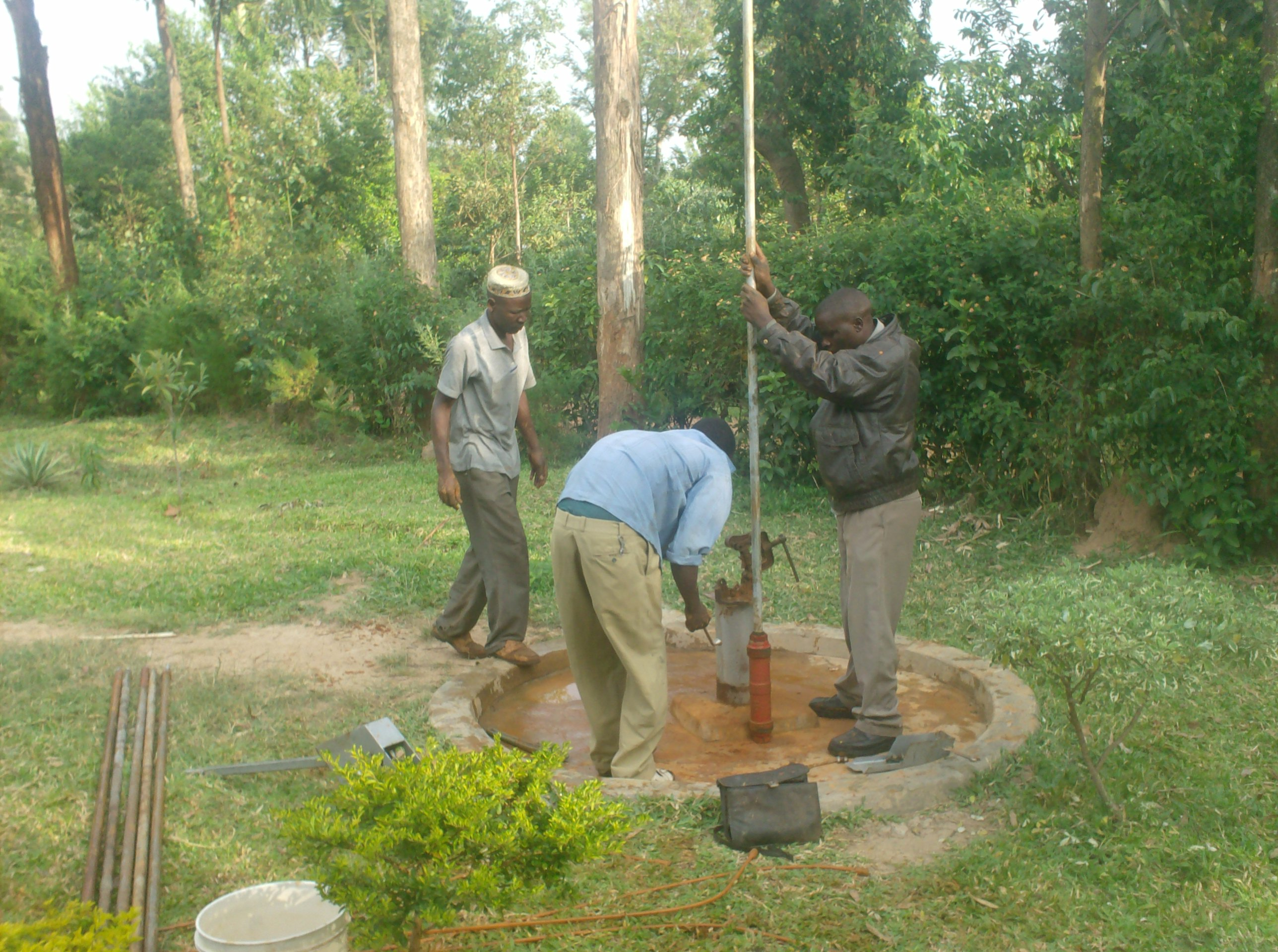 The Water Project : emusungururu-communitywell-connecting-of-gi-pipes-to-pump-cylinder