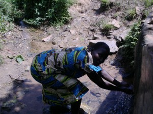 The Water Project : karima-mbakalo-a-quick-drink-from-the-spring-before-the-long-walk-home-carrying-water