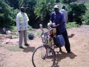 The Water Project : musembe-mbakalo-icfem-staff-member-dominic-yellow-jacket-meets-villagers-collecting-water-1280x960