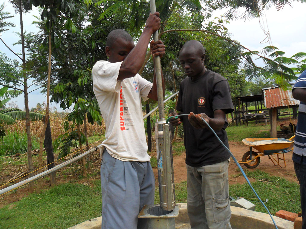 The Water Project : putting-the-pump-inside-the-well-for-testpumping-emulundu