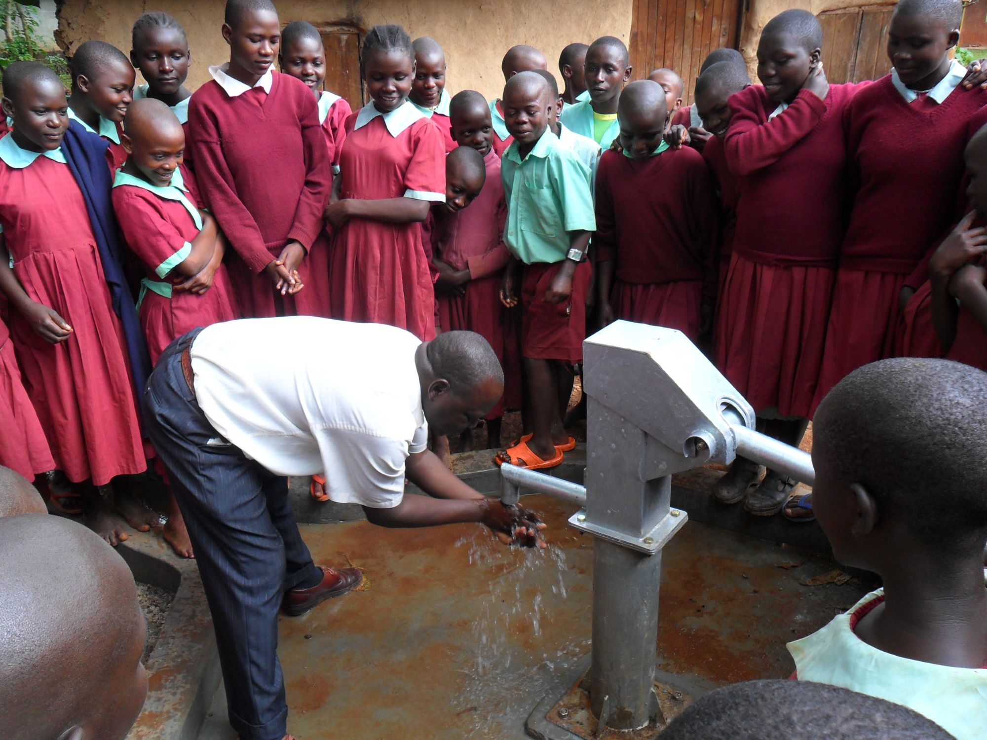 The Water Project : deputy-headteacher-enjoys-the-water-after-handing-over-of-hirumbi-well-2