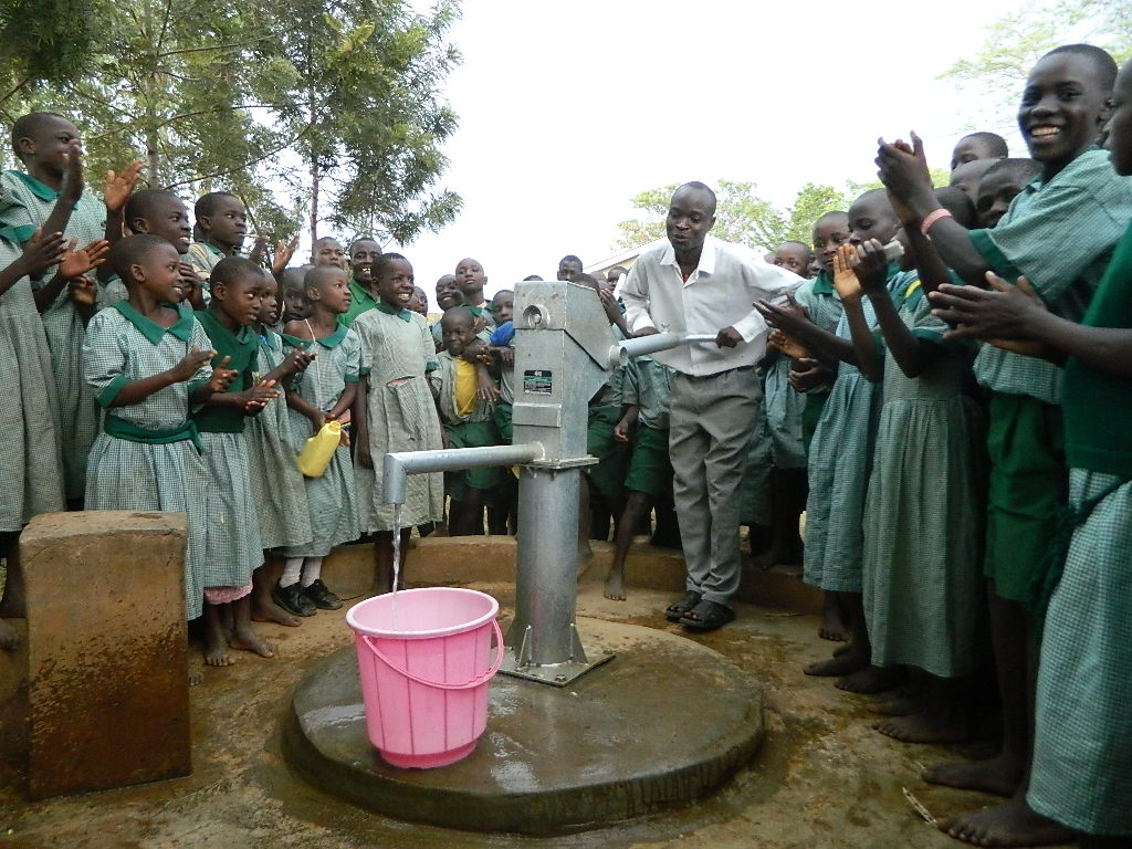 The Water Project : kenya4246-46-the-senior-teacher-pumping-the-water-2