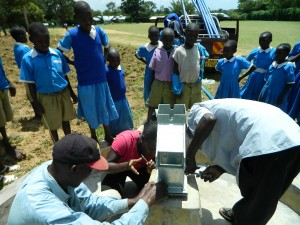 The Water Project : kenya4245-30-tightening-the-bolts-on-the-pump-2