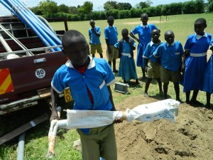 The Water Project : kenya4245-33-a-pupil-helps-to-carry-the-new-pump-2