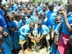 The Water Project : kenya4245-36-handing-over-the-rehabilitated-water-source-to-the-pupils-2