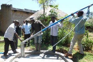 The Water Project : kenya4252-20-community-members-taking-part-in-installing-the-pump