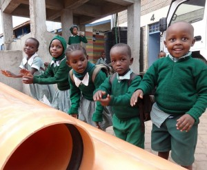 The Water Project : kenya-pamojamashimoni-14-kids-marveling-at-the-water-pipes