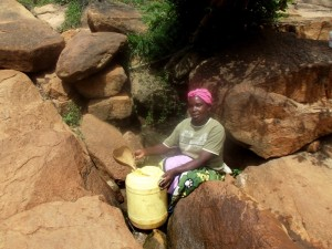 The Water Project : kenya4307-kee-woman-fetching-water-from-a-rock-01