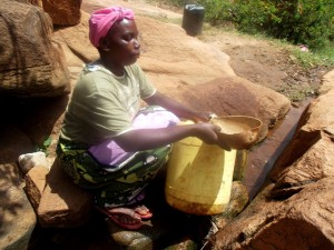 The Water Project : kenya4307-kee-woman-fetching-water-from-a-rock-15