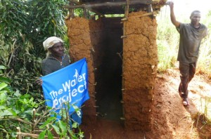The Water Project : kenya4291-14-mary-kisanji-with-her-new-san-plat-and-partially-built-latrine