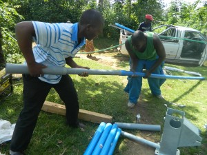 The Water Project : kenya4258-24-fixing-the-cylinder-to-the-pipe-before-installation-at-eshikulu-community