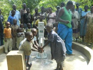The Water Project : kenya4258-32-eshikulu-community-members-and-children-are-happy-to-see-water-flowing-from-the-pump