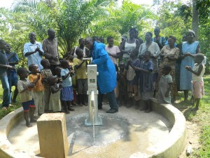 The Water Project : kenya4258-39-protas-machembe-of-bwp-demonstrating-to-the-members-on-how-to-use-the-pump