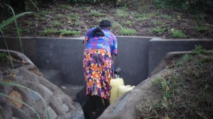 The Water Project : kenya4289-18-nancy-drawing-water-from-lihanda-spring-after-protection