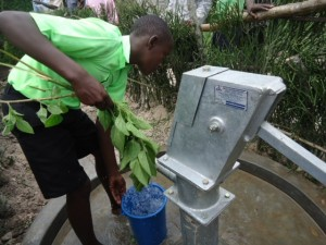 The Water Project : uganda6056-16-community-leaning-around-the-source