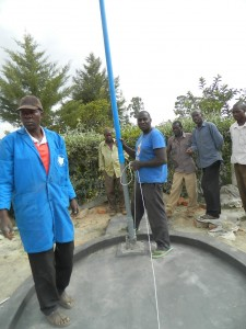The Water Project : kenya4281-16-inserting-the-cylinder-and-the-rising-main-pipes