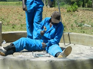 The Water Project : kenya4319-35-mansons-installing-the-gasket-rubber-and-the-anchor-bolts