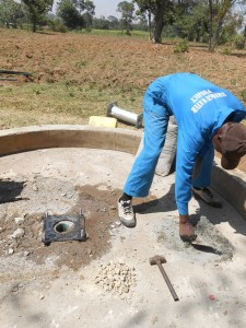 The Water Project : kenya4319-36-mansons-installing-the-gasket-rubber-and-the-anchor-bolts
