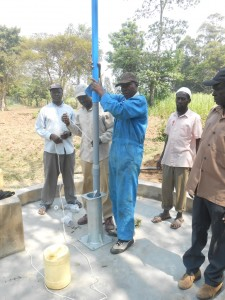 The Water Project : kenya4319-46-installing-the-cylinder