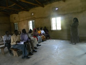 The Water Project : kenya4320-09-janet-of-bwp-adressing-the-comm-members-of-utende