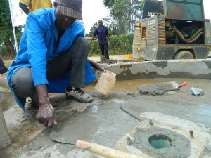 The Water Project : kenya4320-15-obote-plastering-the-well-pad-in-utende