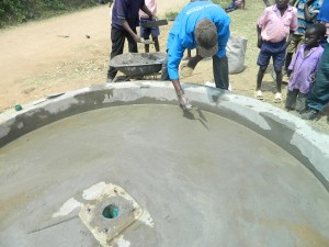 The Water Project : kenya4320-16-plastering-the-well-at-utende