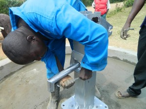 The Water Project : kenya4320-26-stanley-tightening-the-bolts-of-the-pump