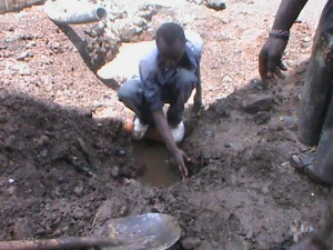 The Water Project : kenya-pamojamashimoni-38-the-grounds-man-indicates-where-the-water-pipes-would-pass-through-2