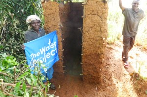 The Water Project : kenya4285-19-mary-proudly-holds-up-a-twp-sign-as-she-shows-us-her-new-latrine-still-under-construction-and-sanplat