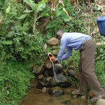 The Water Project: Mumuli Community -  Community Member Is Washing His Hands From Unprotected Spring At Mumuli Spring