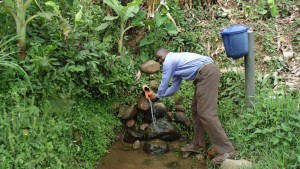 The Water Project:  Community Member Is Washing His Hands From Unprotected Spring At Mumuli Spring