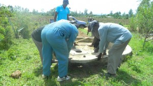 The Water Project : kenya4338b-81-bridge-water-masonary-team-lifting-the-well-cover