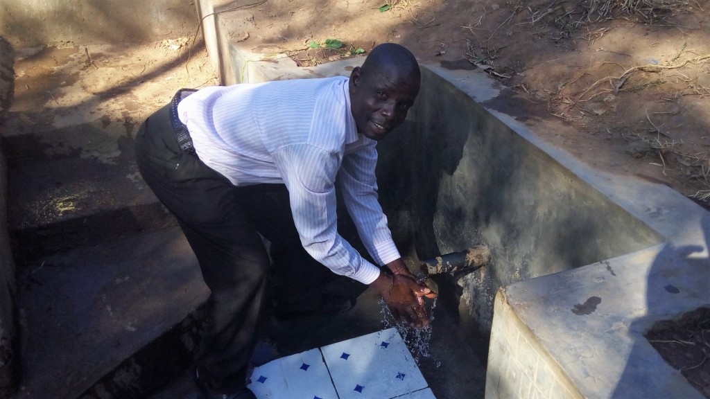 Mr. Litali enjoying clean safe water from the protected Litali SPRING