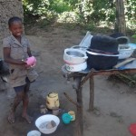 The Water Project: Shitungu Community A -  Shanila Poses Before Her Improvised Dish Rack