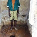 The Water Project : 12-kenya4657-boy-inside-latrine-no-shoes