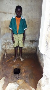 The Water Project:  Boy Inside Latrine No Shoes