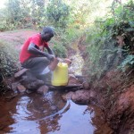 The Water Project: Eluhobe Community -  Mr Andrew Nyanje Fetches Water From Amadi Spring