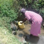 The Water Project: Eshiakhulo Community -  Woman Drawing Water At Omar Sakwa Spring