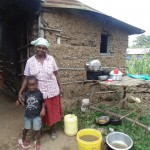 The Water Project: Murumba Community -  Mother And Son Next To Dish Rack