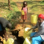 The Water Project: Mutambi Community, Kivumbi Spring -  Fetching Water