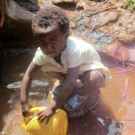 The Water Project: Mutambi Community, Kivumbi Spring -  Anita Fetching Water