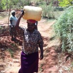 The Water Project: Wanzuma Community -  Catherine Lumadede Balancing Water On Her Head