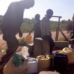 The Water Project: Eshisuru Primary School -  Community Using The Nearby Well