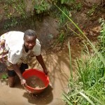 The Water Project : 10-kenya4728-woman-draining-stagnant-water