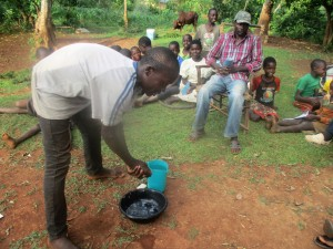 The Water Project : 11-kenya4710-silas-mutie-demonstrates-how-to-wash-hands-with-water-and-ash